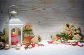 Svíčková lucerna, jedlové větve, cetky, perníkové sušenky a další vánoční ozdoby uspořádané na bílém dřevěném pozadí, kopírovací prostor