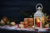 Vánoční dekorace se svíčkou lucernou, dárky, jedlovými větvemi, cetkami a perníkovými hvězdami uspořádanými na tmavomodrém dřevěném pozadí, kopírovací prostor