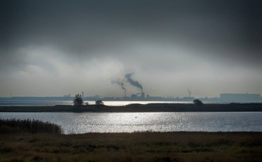 View from the German island Poel over the Baltic Sea to the industrial port of Wismar on a dreary cloudy day, copy space in the dark sky