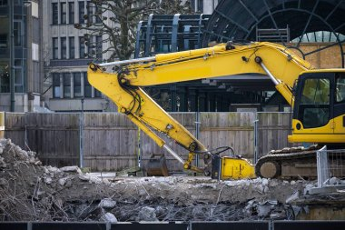 Yellow excavator on a construction site in the city