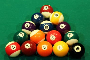 Sports game of billiards on a green cloth. Multi-colored billiard balls in the shape of a triangle with numbers on the pool table. Active leisure and entertainment. Billiards billiard balls close up.