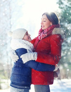 Christmas happy family, son child hugs his mother in winter sunn