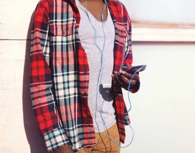 Fashion african man listens to music on a smartphone in the city