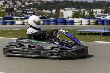Karting Championship. Driver in karts wearing helmet, racing suit participate in kart race. Karting show. Children, adult racers karting.
