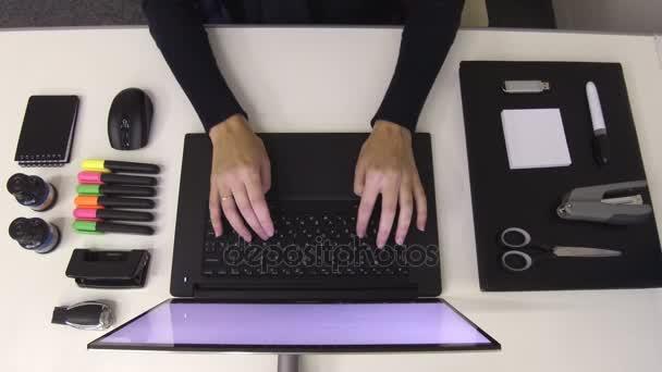 Černobílé kancelářské potřeby. Žena psaní na notebooku