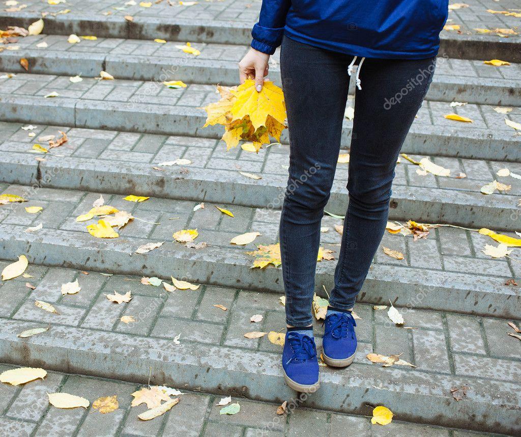 db96f3e8ae1 Jambes de sportive blue jeans et baskets. Femme en braker vent bleu tenant  dans la main les feuilles– images de stock libres de droits