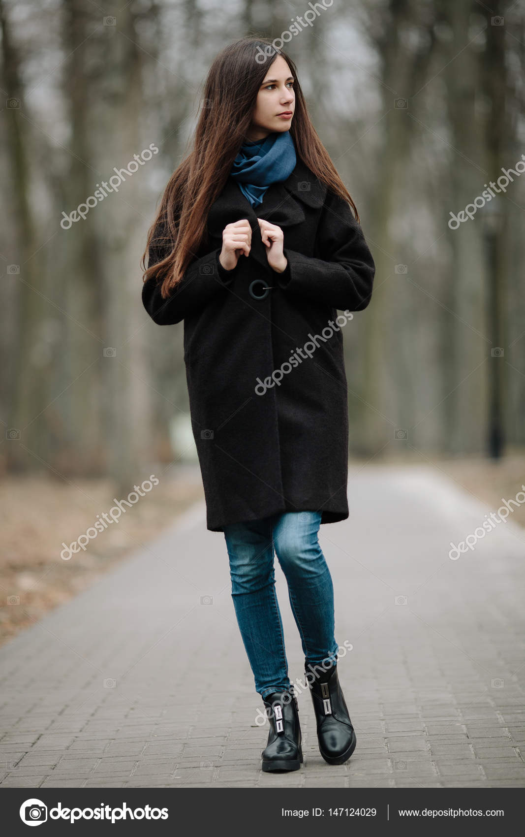 51c5768b5 Young beautiful girl in a black coat and blue scarf for a walk in ...