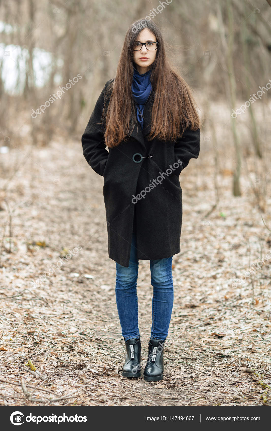 70a04dad9 Young beautiful girl in a black coat blue scarf glasses walking in ...