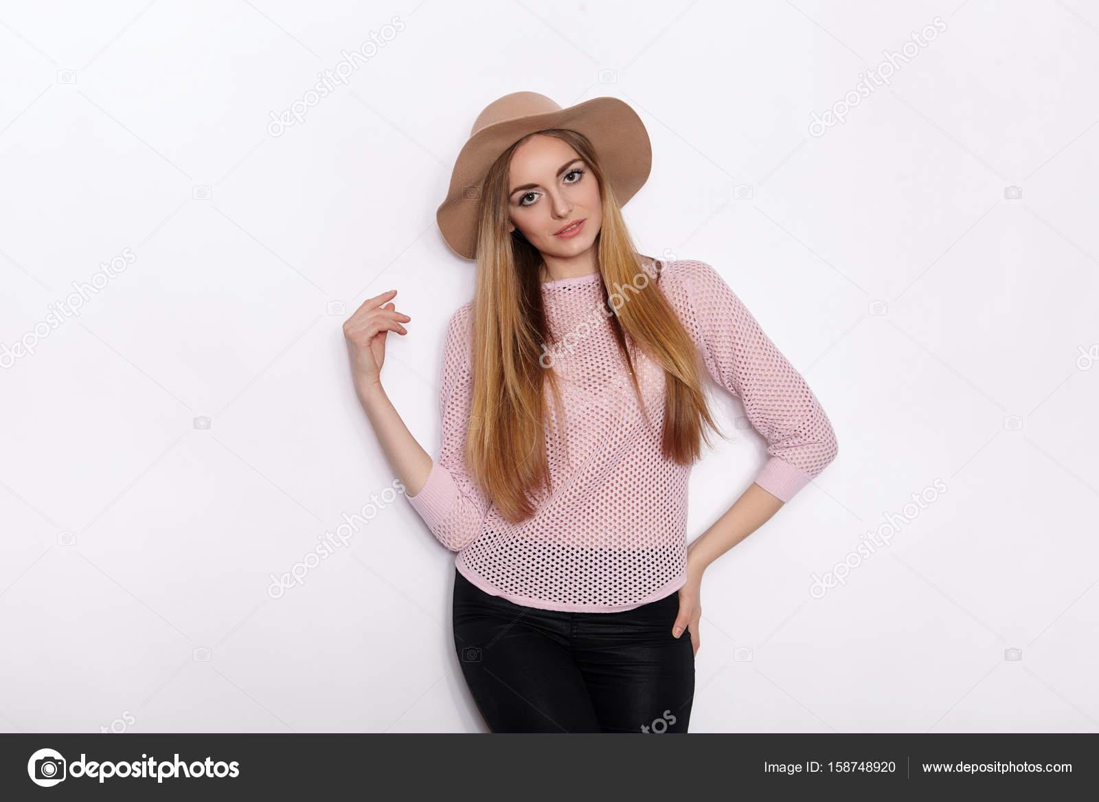 47c7dc531 Linda y elegante mujer joven hermosa rubia en ropa de moda practicar poses  de modelo y mirando lejos sonriendo mientras está parado sobre fondo de  pared ...