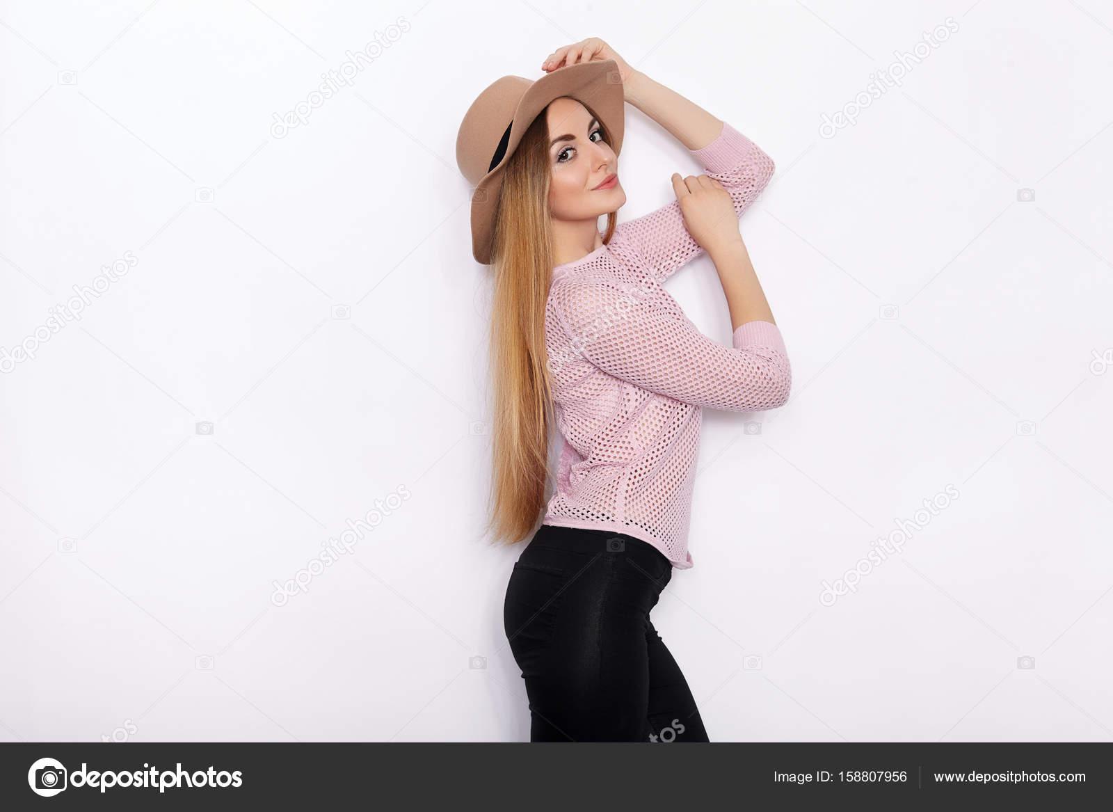 Süß und stylish schöne junge blonde Frau in trendige Kleidung Model Posen  üben und wegschauen mit Lächeln im stehen gegen die weiße Wand Hintergrund  — Foto ... 5b745b7d92