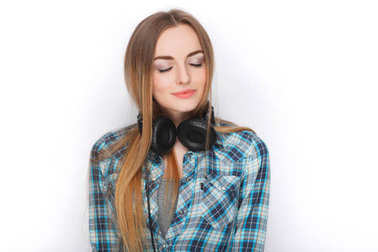 Headshot of a young adorable blonde woman in blue plaid shirt enjoying listening music to big professional dj headphones.
