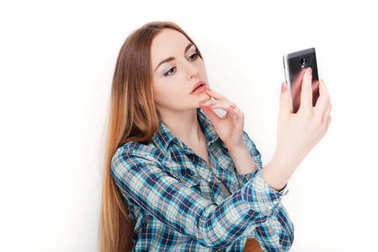 Portrait of a young adorable blonde woman in blue plaid shirt enjoying doing selfie on smartphone.