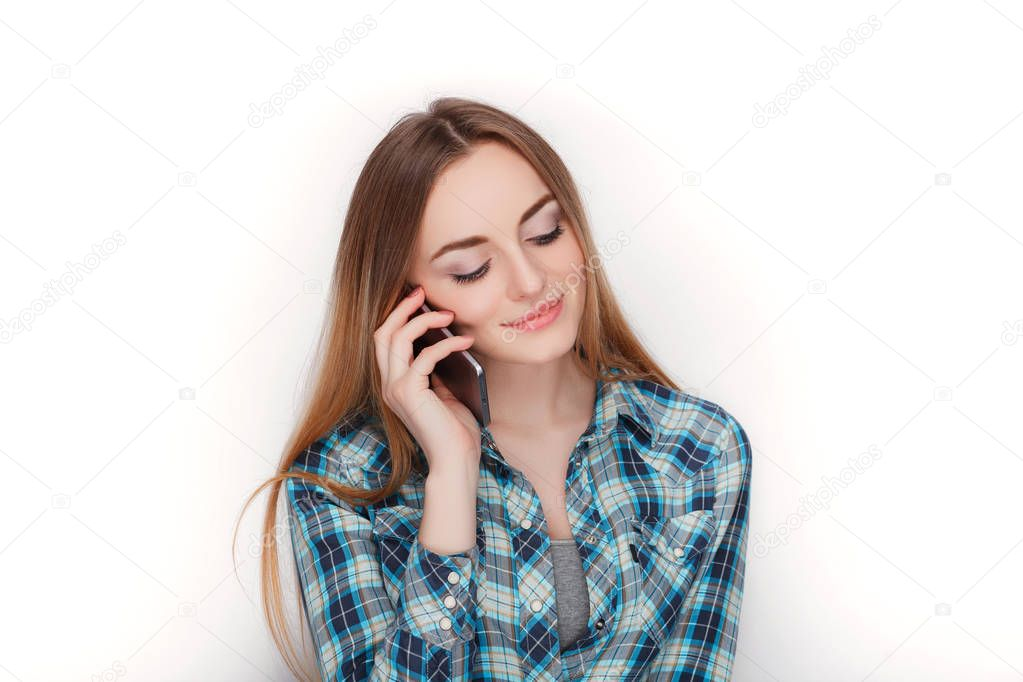 Portrait of a young adorable blonde woman in blue plaid shirt enjoying having emotional conversation on smartphone.