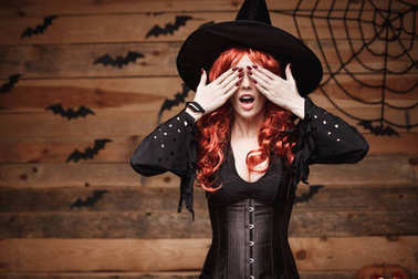 Halloween witch concept - Happy Halloween red hair Witch holding hands closing eyes posing over old wooden studio background.