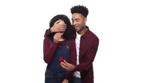 African American ask his girlfriend for proposal engagement with wedding ring over white studio background.