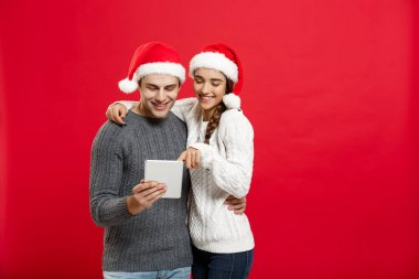 Christmas Concept - Young handsome and beautiful couple enjoy playing on tablet in christmas day