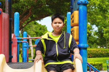 Sport and lifestyle Concept: Young asian boy sitting on playground at outdoor playground.