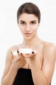 Szépség ifjúsági Skin Care koncepciót - gyönyörű kaukázusi nő arca álló bemutató bőrápoló krém jar, fehér háttérhez képest közelről.