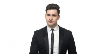 Young handsome businessman in suit says no shaking his finger , rejection isolated over white background.