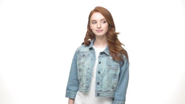Životní styl koncept: Happy červenovlasá dívka v džínové ukazující mírové gesto k fotoaparátu stoje izolované na bílém pozadí