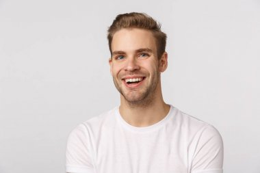 """Картина, постер, плакат, фотообои """"Dreamy charming blond caucasian guy with blue eyes and bristle, laughing and smiling from happiness and delight, express positive emotions, look cheerfully and upbeat, white background"""", артикул 326080676"""