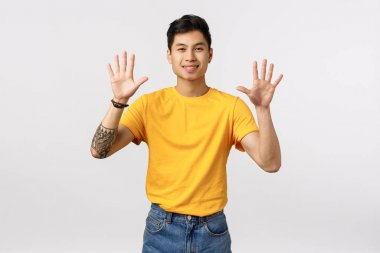 Cheerful, friendly-looking attractive asian man in yellow t-shirt, with tattoos, showing ten fingers, raising arms, order dozen, smiling joyfully, standing white background upbeat