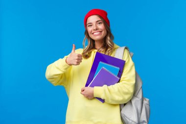 Sounds good. Cheerful cute and smart caucasian girl in red beanie studying hard for exams, encourage student keep up, show thumbs-up in like or approval, hold notebook and backpack