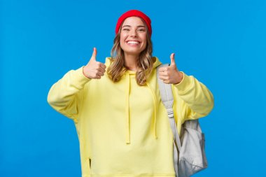 Sounds good, deal. Cheerful happy and smiling hipster girl in red beanie and yellow hoodie, approve idea, agree with friends picking where hang out after classes, hold backpack, blue background