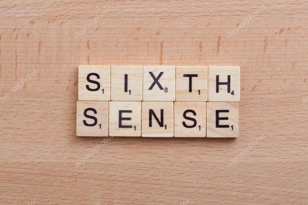 scrabble letters spelling the word sixth sense stock photo