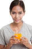Mladá asijská žena pít pomerančový džus