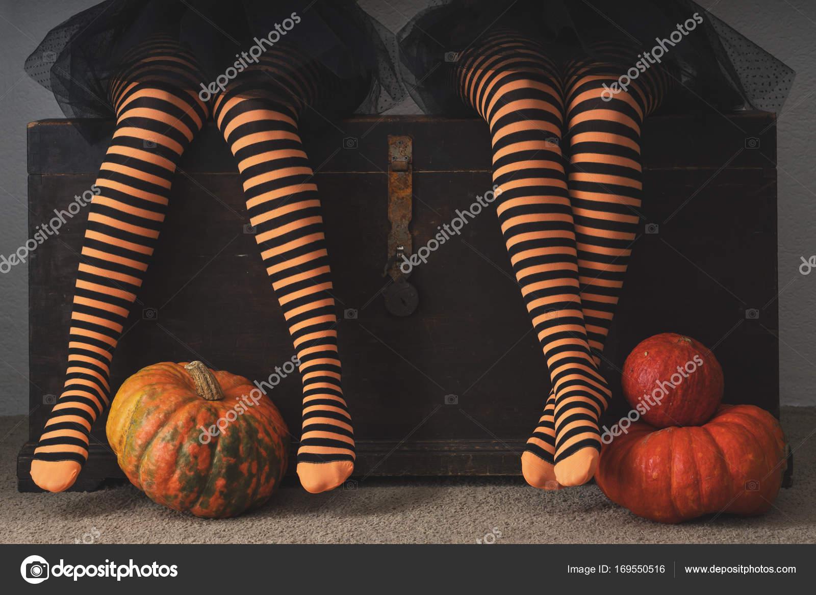Fröhliches Halloween! Weibliche Füße in Strümpfen mit einem orange ...