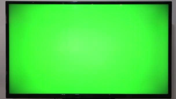 Osoba ukazující dálkově TV a mačkající tlačítka před televizorem se zelenou obrazovkou