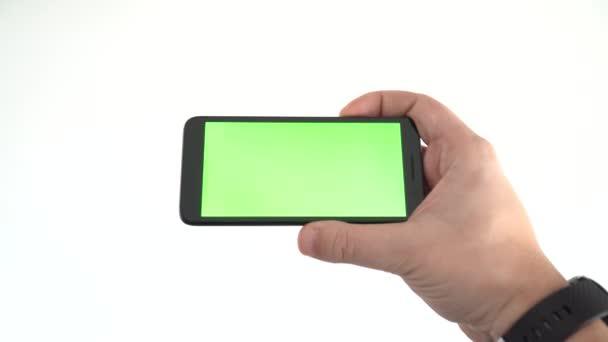 Tartása egy okostelefon egy üres képernyő egy vízszintes helyzetben elszigetelt fehér háttér. Videókoncepció megtekintése.