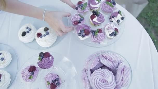 Žena si čerstvé pečené vdolky z cínu muffiny a položte je na talíř, vyloží košíčky v přírodě, jídlo na stole