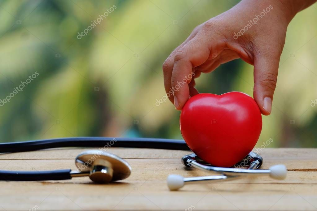 Hand touching red heart and stethoscope on old wood table