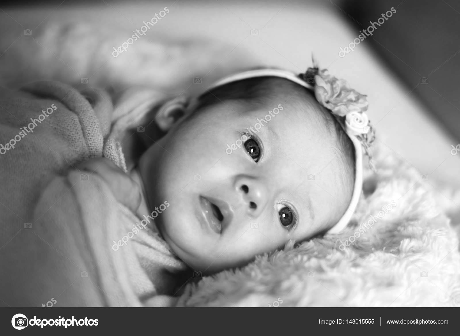 Cute newborn baby girl in the bed black and white photo by
