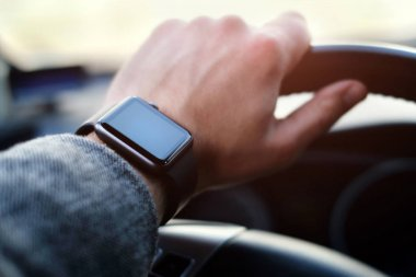 businessman driving a car with smart watch