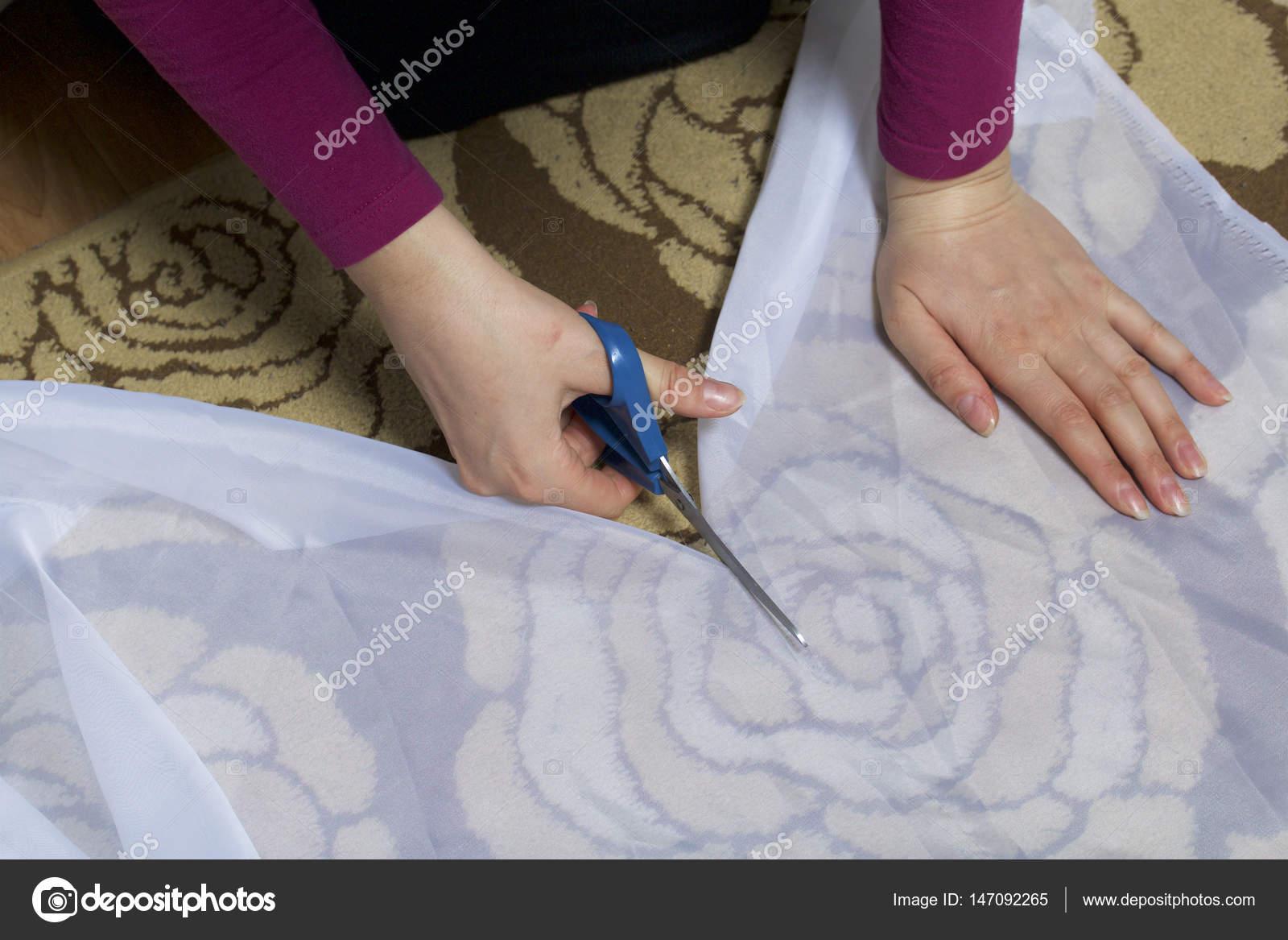 De vrouw snijdt het weefsel met een schaar voor naaien gordijnen op ...