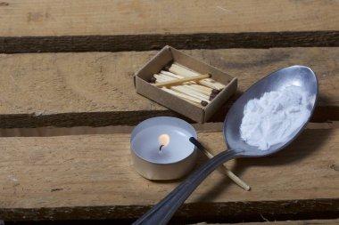 Uyuşturucu salgını. Yemek pişirmek için uyuşturucu içine bir kaşık dökülür, bir ahşap kutu üzerinde yatıyor. Bir mum alevi yakındaki yanıyor ve maçlar yalan.
