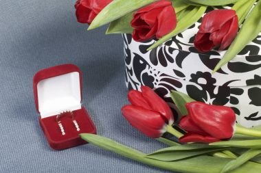 Gifts for loved ones. A bouquet of red tulips is scattered on a corpse with a pattern of white and black. Nearby is a red velvet box with a ring and earrings. On the gray tissue surface.