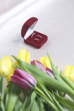 Gifts for loved ones. A bouquet of yellow and pink tulips is scattered on a light surface. Nearby is an open velvet box of red color with gold jewelry.