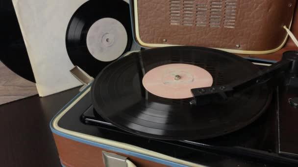 Eine Schallplatte rotiert auf einer Platte eines Plattenspielers. Der Pickup-Kopf hebt sich, wenn die Wiedergabe endet. Ein Mann stellt einen Pickup auf ein Gestell.