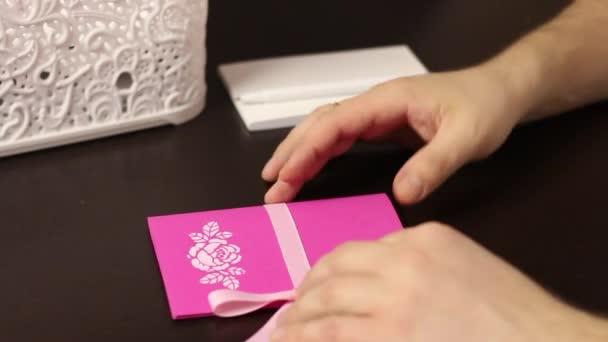Egy férfi megpörget egy üdvözlőlapot a kezében. Az asztalra teszi. Közelkép..