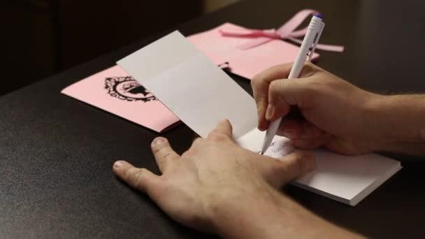 Egy férfi megpörget egy üdvözlőlapot a kezében. Az asztalra teszi. Átírja a címzett vezetéknevét egy noteszbe. Közelkép..