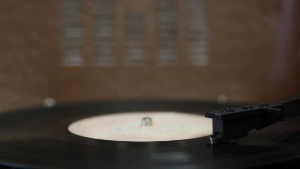 A bakelit lemez egy elektromos lemezjátszón forog. A lejátszás véget ér, a felszedő feje felemelkedik, és megáll a rekord forgása..
