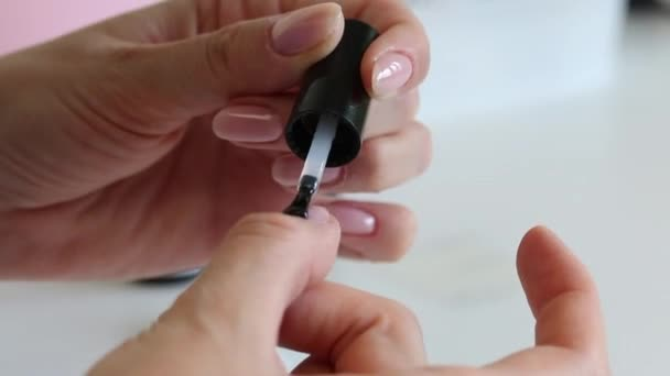 Děvče dělá manikúru v izolaci. Jemně naneste gel na nehet palce. Detailní záběr