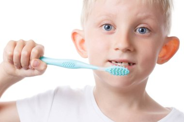 little boy with toothbrush in hands, child cleans teeth