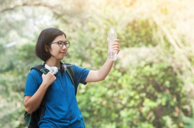 Asian woman hiker with backpack holding bottle of water
