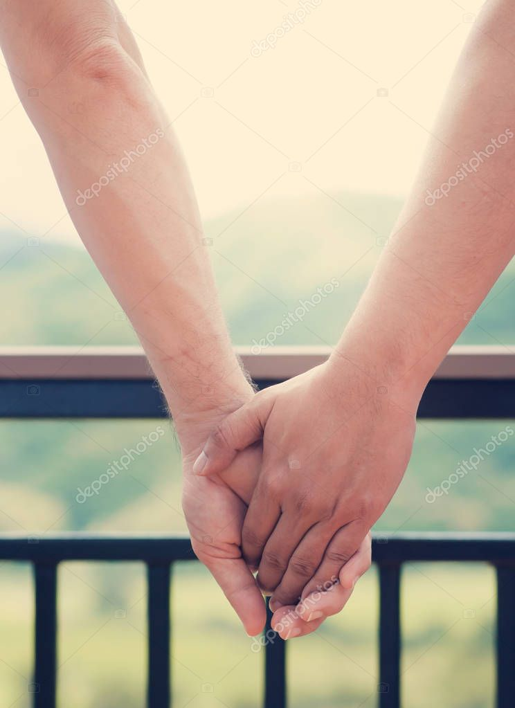 Close up of men gay couple holding hands on green natural backgr