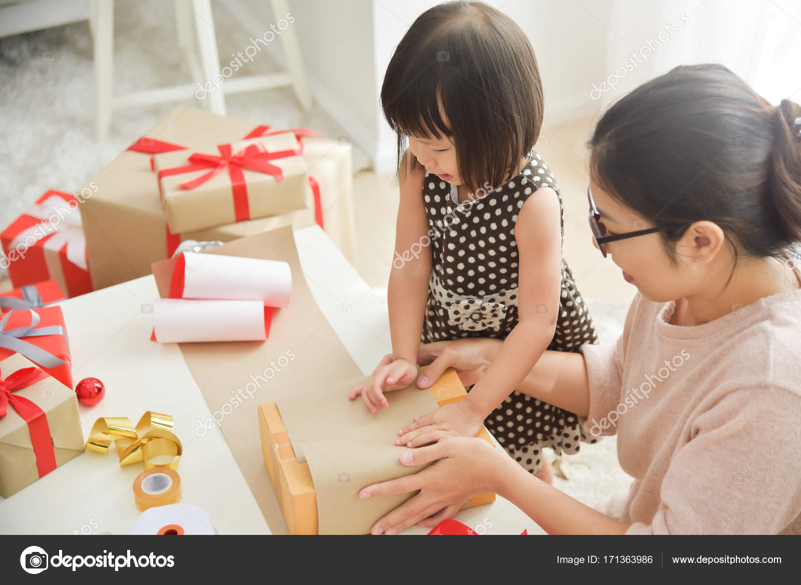 Young Mother And Her Daughter Wrapping A Gift Box For Birthday Christmas New Year In White Room Happy Asian Family At The House Copy Space
